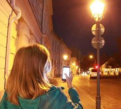 Person with smartphone and street lighting